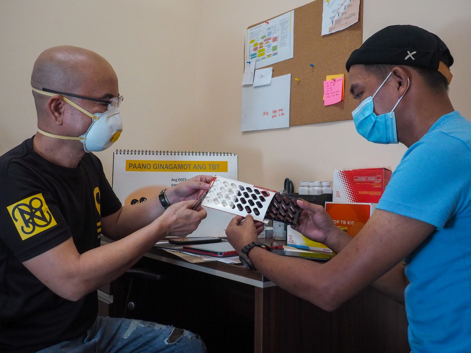 Nurse Anton shows Angelito how to use the 99DOTS medication sleeve.